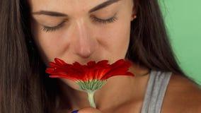 Piękna młoda kobieta ono uśmiecha się joyfully podczas gdy wąchający kwiatu zbiory wideo