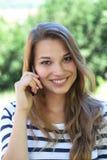 Piękna młoda kobieta ono uśmiecha się na telefonie w parku zdjęcia royalty free