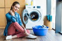 piękna młoda kobieta ono uśmiecha się przy kamerą podczas gdy siedzący blisko pralki i klingerytu basenu zdjęcia stock