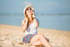 Piękna młoda kobieta opowiada dalej przy plażą fotografia royalty free