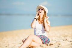 Piękna młoda kobieta opowiada dalej przy plażą Obraz Royalty Free
