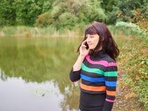 Piękna młoda kobieta opowiada na mądrze telefonie przy jesień parkiem Pre zdjęcie royalty free