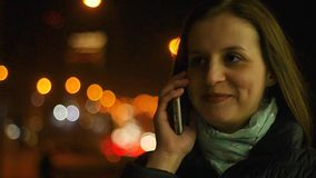 Piękna młoda kobieta opowiada na smartphone, chodzi przez nocy miasta zbiory