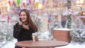 Piękna młoda kobieta opowiada na telefonie i pije gorącej herbaty podczas Bożenarodzeniowego jarmarku zbiory wideo