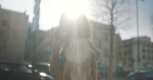 Piękna młoda kobieta opowiada na telefonie podczas słonecznego dnia zbiory