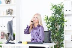 Piękna młoda kobieta opowiada na telefonie w biurze Fotografia Royalty Free