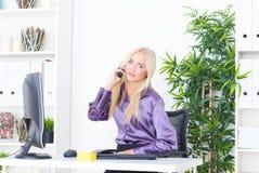 Piękna młoda kobieta opowiada na telefonie w biurze Obraz Stock