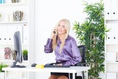 Piękna młoda kobieta opowiada na telefonie w biurze Zdjęcia Stock