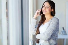 Piękna młoda kobieta opowiada na telefonie w domu Zdjęcie Royalty Free