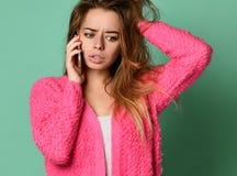 Piękna młoda kobieta opowiada telefonem komórkowym na lekkim tle zdjęcie stock