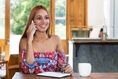 Piękna młoda kobieta opowiada z innymi kobietami przy telefonem zdjęcie stock