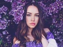 Piękna młoda kobieta otaczająca kwiatami obrazy royalty free