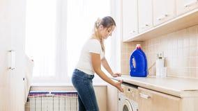Piękna młoda kobieta otwiera pralka zbiornika dla płuczkowego proszka i softener Obraz Stock