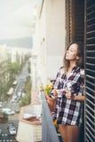 Piękna młoda kobieta pije filiżankę kawy lub herbaty podczas gdy stojący na balkonie Obrazy Stock
