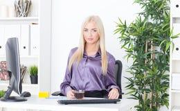 Piękna młoda kobieta pije gorącej herbaty przy biurem Zdjęcia Royalty Free