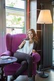 Piękna młoda kobieta pije kawę w restauraci podczas gdy smil fotografia royalty free