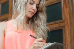 Piękna młoda kobieta pisze w notatniku Zdjęcie Stock