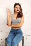 Piękna młoda kobieta podnosi jego prawą rękę up w szkole Biały ściana z cegieł, nie obraz stock