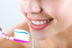 Piękna młoda kobieta podnosi jego zęby Zdjęcia Royalty Free
