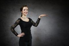 Piękna młoda kobieta pokazuje twój produkt Zdjęcie Royalty Free