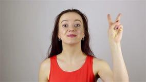 Piękna młoda kobieta pokazuje zwycięstwa ono uśmiecha się i znaka zbiory