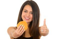 Piękna młoda kobieta pozuje łasowanie hamburger podczas gdy dawać kciukowi do kamery, ono uśmiecha się szczęśliwie, biały pracown Zdjęcie Royalty Free