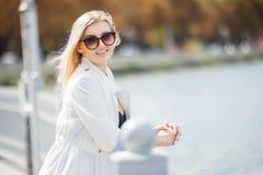 Piękna młoda kobieta pozuje jako wzorcowa pozycja na bulwarze blisko morza lub oceanu Damy być ubranym przypadkowy i okulary prze Zdjęcie Royalty Free