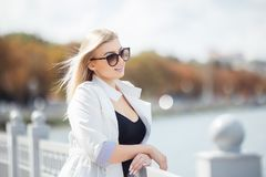 Piękna młoda kobieta pozuje jako wzorcowa pozycja na bulwarze blisko morza lub oceanu Damy być ubranym przypadkowy i okulary prze Zdjęcia Stock