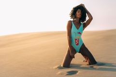 Piękna młoda kobieta pozuje na piasku w pustynne diuny Fotografia Royalty Free