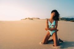 Piękna młoda kobieta pozuje na piasku w pustynne diuny Zdjęcia Stock