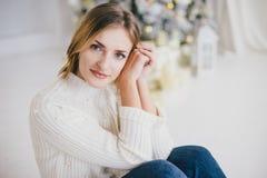 Piękna młoda kobieta pozuje pod choinką Zdjęcie Royalty Free