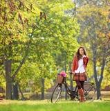 Piękna młoda kobieta pozuje w parku z jej bicyklem Obraz Stock