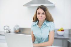 Piękna młoda kobieta pracuje z jej notatnikiem ono uśmiecha się przy kamerą Zdjęcie Royalty Free