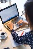 Piękna młoda kobieta pracuje z laptopem w jej biurze Obrazy Stock
