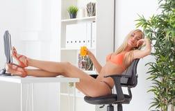 Piękna młoda kobieta przy biurem w bikini sen Obraz Stock