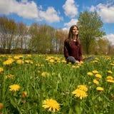 Piękna młoda kobieta relaksuje na łące z wiele dandelions w wiosny słońcu Niski kąt strzelający z niebieskim niebem fotografia stock