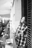 Piękna młoda kobieta relaksuje na balkonie z miasto widokiem trzyma filiżankę kawy lub herbaty Fotografia Stock