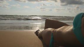 Piękna młoda kobieta relaksuje na dennym brzeg podczas wakacje podróży Ocean fala myje nad garbnikującymi żeńskimi ciekami Zdjęcia Royalty Free