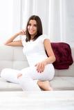 Piękna młoda kobieta relaksuje w domu na kanapie obrazy stock