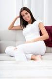 Piękna młoda kobieta relaksuje w domu na kanapie zdjęcie royalty free