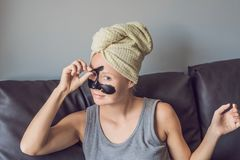 Piękna młoda kobieta relaksuje z twarzy maską w domu Szczęśliwa radosna kobieta stosuje czerni maskę na twarzy Obraz Royalty Free