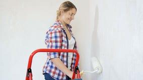 Piękna młoda kobieta renovaating jej nowego mieszkanie Młoda dziewczyna obrazu ściany przy jej pokojem zbiory