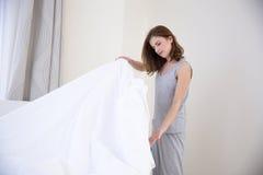 Piękna młoda kobieta robi łóżku fotografia stock