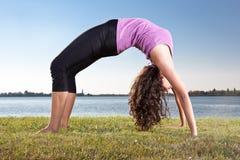 Piękna młoda kobieta robi joga ćwiczeniu na zielonej trawie Zdjęcia Stock