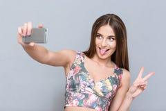 Piękna młoda kobieta robi selfie i pokazuje jęzor Obraz Royalty Free