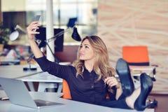 Piękna młoda kobieta robi selfie w jej miejscu pracy Jest relaksująca i stawiająca ona nogi na stole Obraz Royalty Free