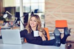 Piękna młoda kobieta robi selfie w jej miejscu pracy Jest relaksująca i stawiająca ona nogi na stole Zdjęcia Royalty Free