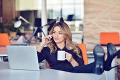Piękna młoda kobieta robi selfie w jej miejscu pracy Jest relaksująca i stawiająca ona nogi na stole Zdjęcia Stock