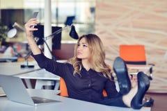 Piękna młoda kobieta robi selfie w jej miejscu pracy Jest relaksująca i stawiająca ona nogi na stole Fotografia Stock