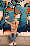Piękna młoda kobieta robi selfie wal outdoors blisko graffiti obraz royalty free
